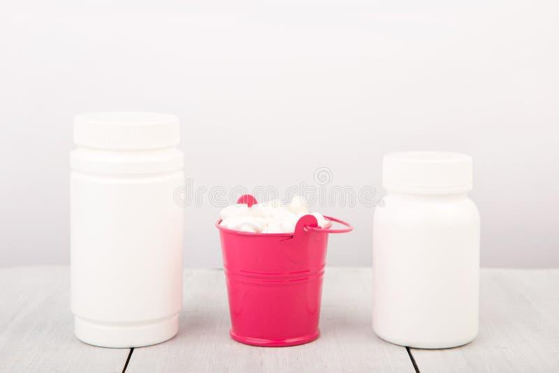 在一个桃红色桶和容器的许多不同的白色药片pil 免版税库存照片