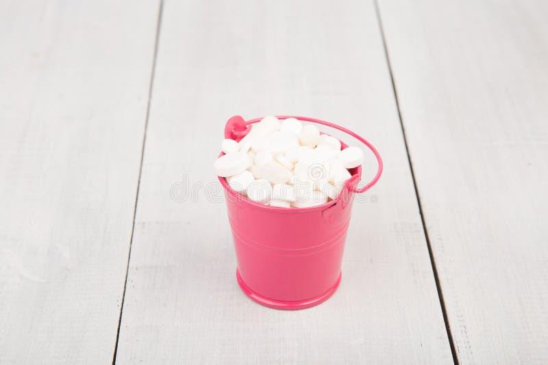 在一个桃红色桶的许多不同的白色药片在木书桌上 免版税库存图片