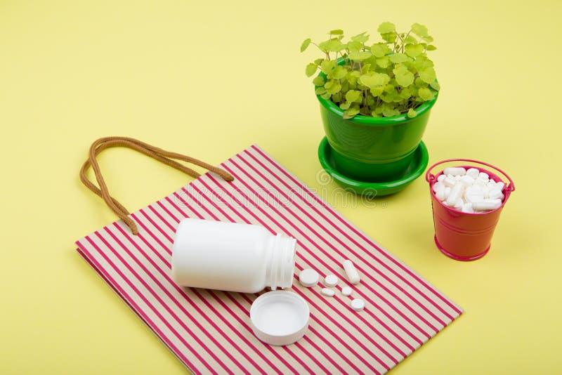 在一个桃红色桶,镶边购物袋的许多不同的药片和 免版税库存照片