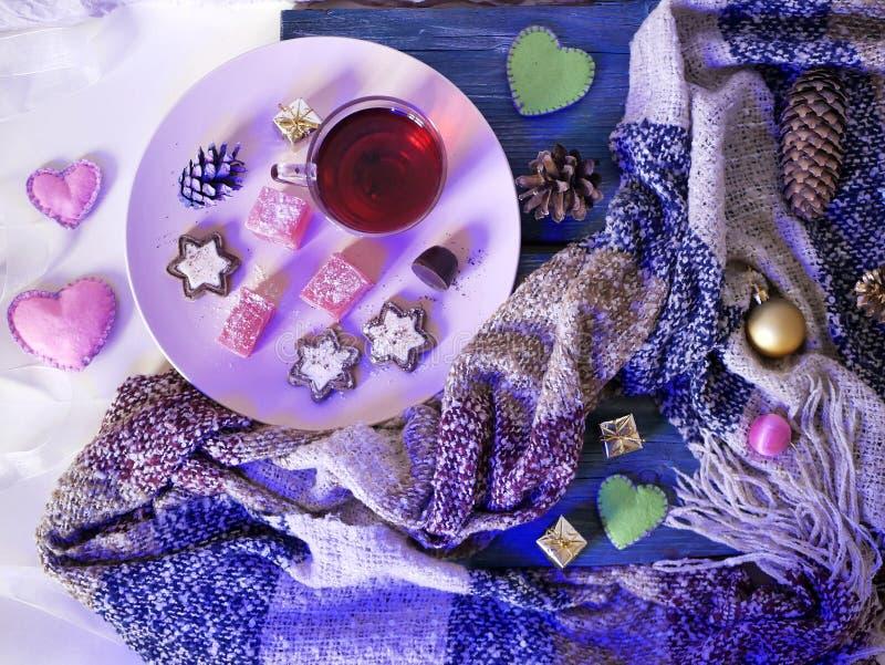 在一个桃红色盘,甜点,巧克力饼干,茶,在圣诞树装饰桌装饰,蓬松围巾,毛毡心脏 免版税库存图片