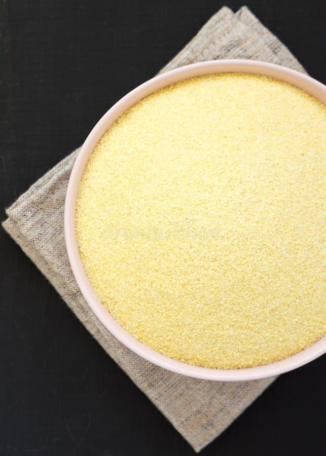 在一个桃红色碗的干粗面粉硬粒小麦面粉在黑背景,顶上的看法 E r 免版税库存图片