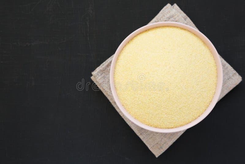 在一个桃红色碗的干粗面粉硬粒小麦面粉在黑背景,顶视图 r r 免版税库存照片