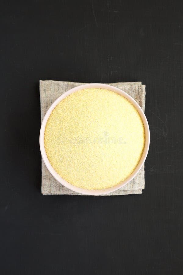 在一个桃红色碗的干粗面粉硬粒小麦面粉在黑表面,顶视图 r r 库存照片