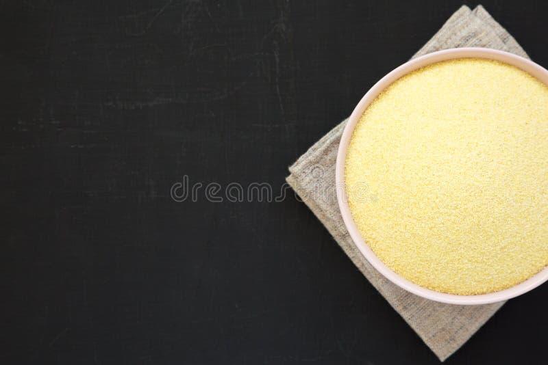 在一个桃红色碗的干粗面粉硬粒小麦面粉在黑表面,顶视图 r r 免版税库存图片
