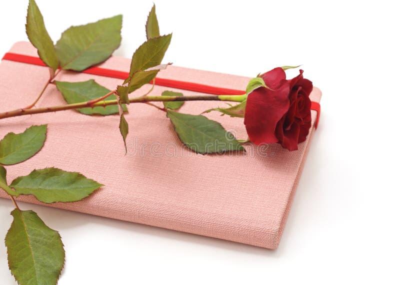 在一个桃红色笔记薄的红色玫瑰 图库摄影