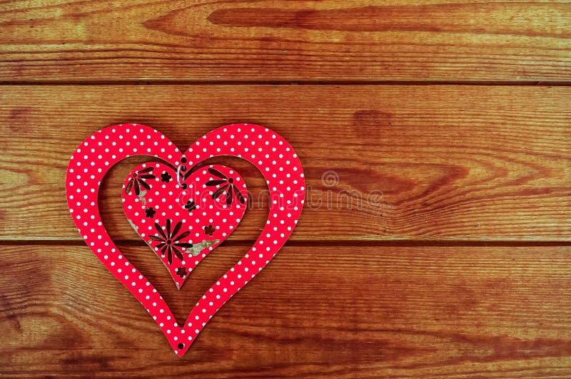 在一个棕色木委员会安置的红色木心脏 库存图片