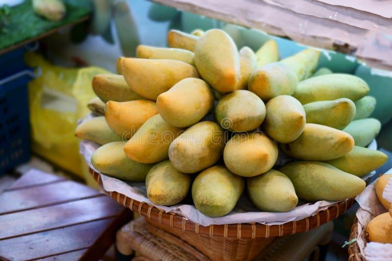 在一个棕色竹篮子的黄色nad绿色芒果在市场上 库存照片