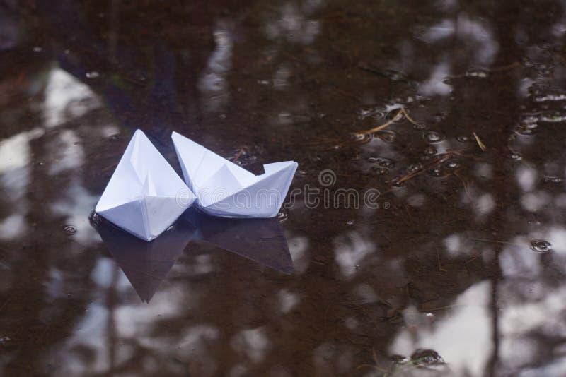 在一个水坑的两条纸小船在秋天 免版税库存图片
