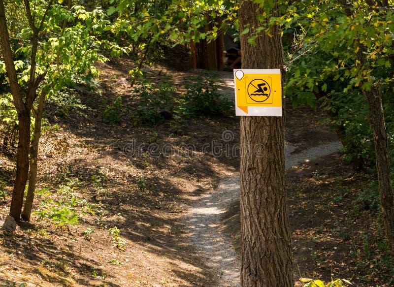 在一个水库附近的尖在足迹的森林,游泳被禁止 免版税库存图片