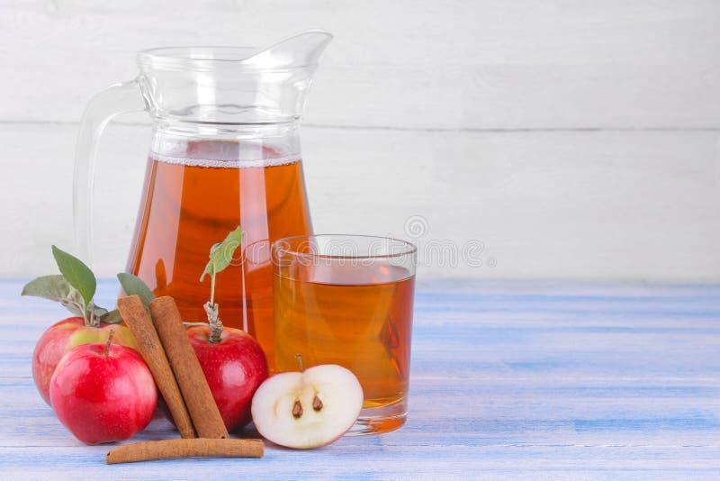 在一个水罐和一块玻璃的苹果汁在新鲜的苹果旁边和肉桂条在一张蓝色木桌上和在白色背景 免版税库存照片