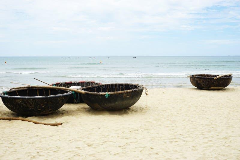 在一个沙滩的几条传统竹小圆舟小船与海浪和天空蔚蓝在越南 库存图片
