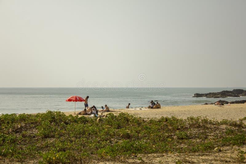 在一个沙滩的鲜绿色的草与休息在一把红色阳伞下的人反对海 库存照片