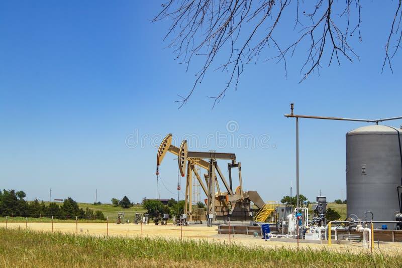 在一个泵站与坦克和机械的两台泵浦起重器有在天际的一些农舍的在与一些t的蓝天下 库存照片