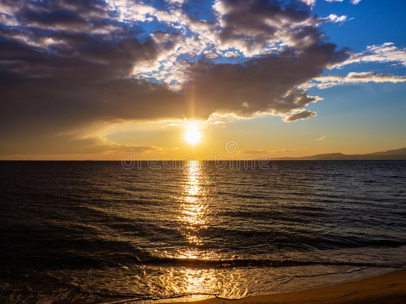 在一个海滩的壮观和美好的日落在希腊 免版税库存照片