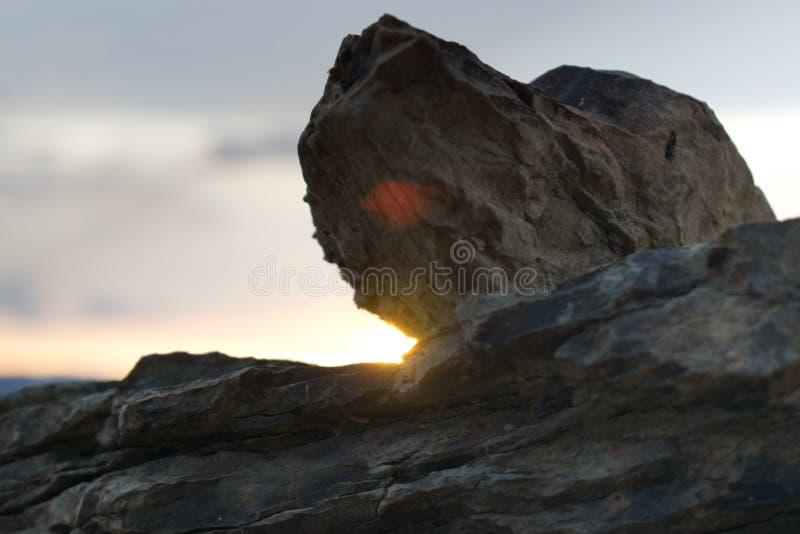 在一个海滩的岩石在日落 免版税库存照片