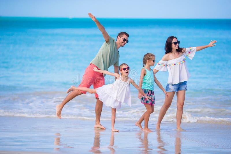 在一个海滩的愉快的美丽的家庭在暑假时 免版税图库摄影
