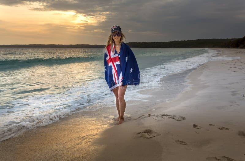 在一个海滩的澳大利亚旗子装饰的妇女在清早 库存图片