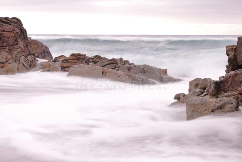 在一个海滩的长的曝光摄影与波浪跳动岩石 图库摄影