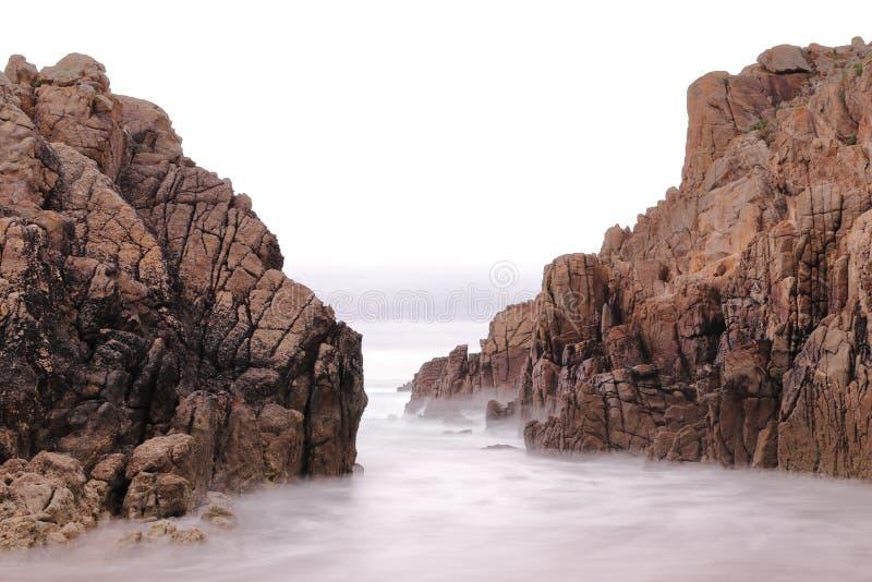 在一个海滩的长的曝光照片在两峭壁之间 免版税库存图片