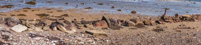 在一个海滩的小卵石在全景 免版税库存图片