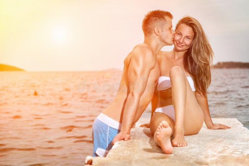 在一个海滩的年轻愉快的夫妇亲吻在日落期间 图库摄影