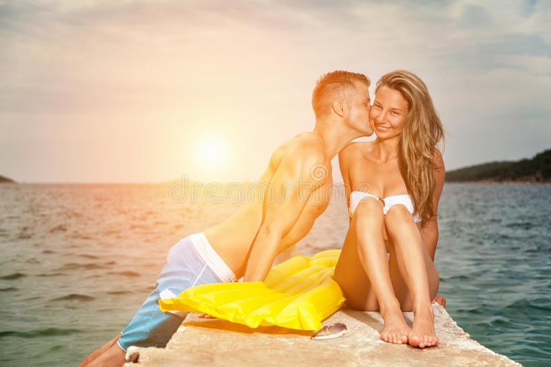 在一个海滩的年轻愉快的夫妇亲吻在日落期间 免版税库存照片