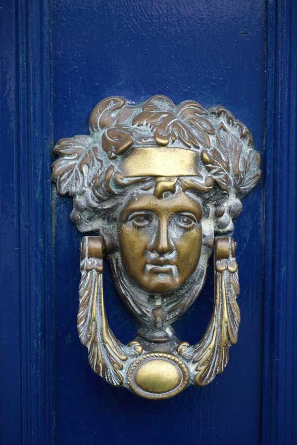 在一个深蓝门的葡萄酒古色古香的黄铜通道门环 免版税库存图片