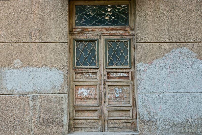在一个混凝土墙上的老灰色棕色闭合的木门 免版税库存图片