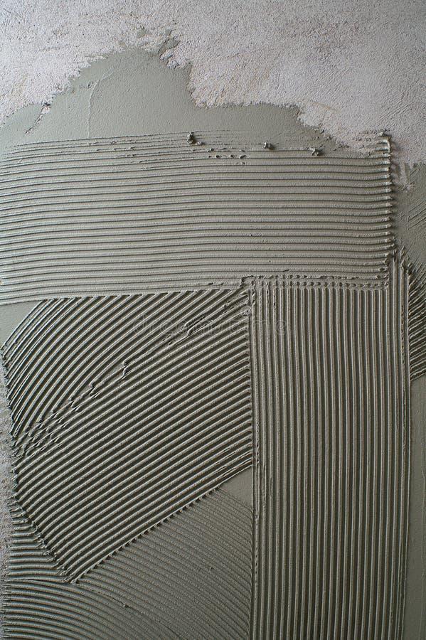 在一个混凝土墙上的被刻凹痕的troweling的灰浆在准备 免版税库存照片