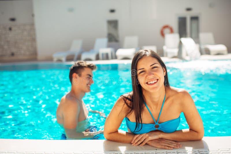 在一个清楚的水池的微笑的快乐的妇女游泳在一个晴天 获得在假期池边聚会的乐趣 享受放松的友好的女性 库存图片
