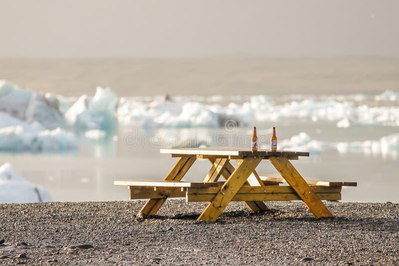 在一个湖前面的松弛啤酒有冰山的 库存图片