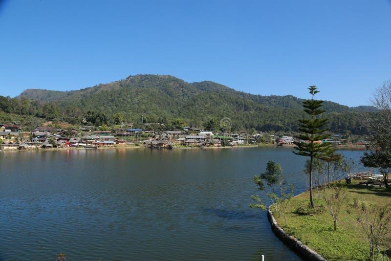 在一个湖旁边的村庄山的 免版税库存图片