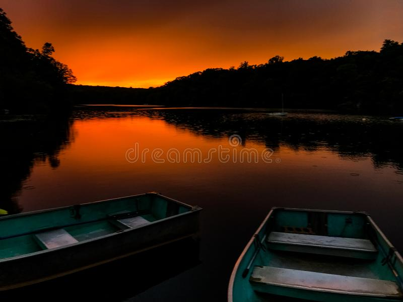 在一个湖的小船日落的 免版税库存图片