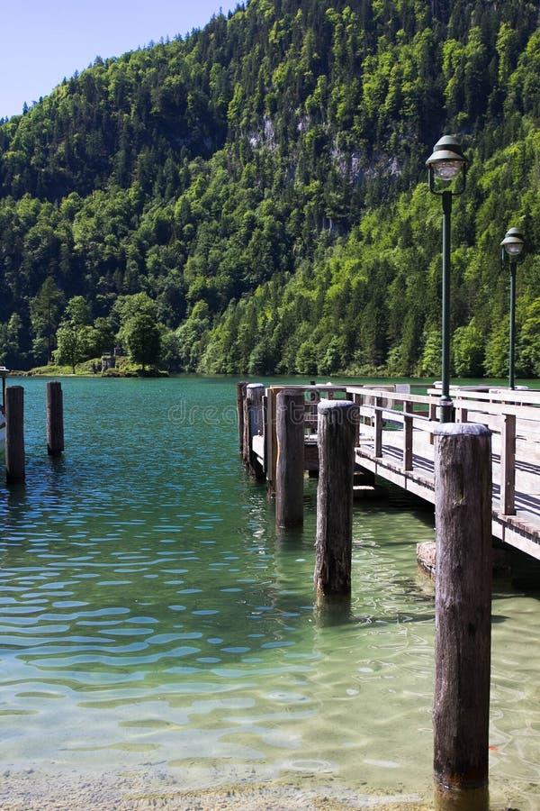 在一个湖的木码头在阿尔卑斯在春天反对山背景  免版税图库摄影