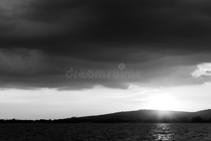 在一个湖的美好的日落,当阳光受到下来阴暗天空 库存图片