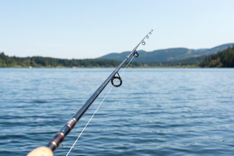在一个湖的钓鱼竿有山的 免版税库存照片