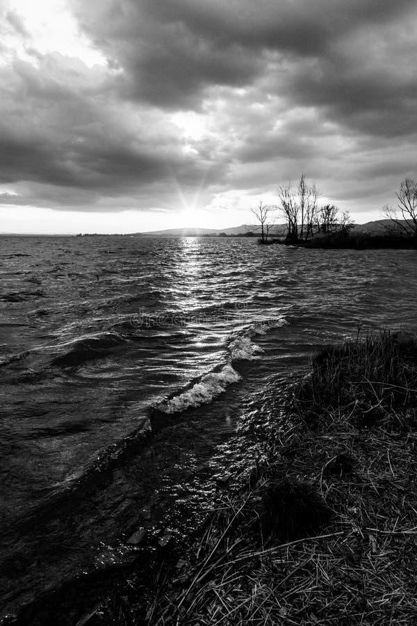 在一个湖的Beautufl日落,当树剪影和太阳受到下来阴暗天空 免版税图库摄影