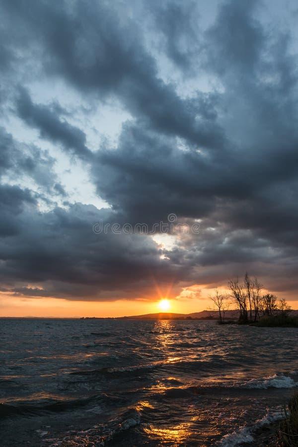 在一个湖的Beautufl日落,当树剪影和太阳受到下来阴暗天空 免版税库存照片