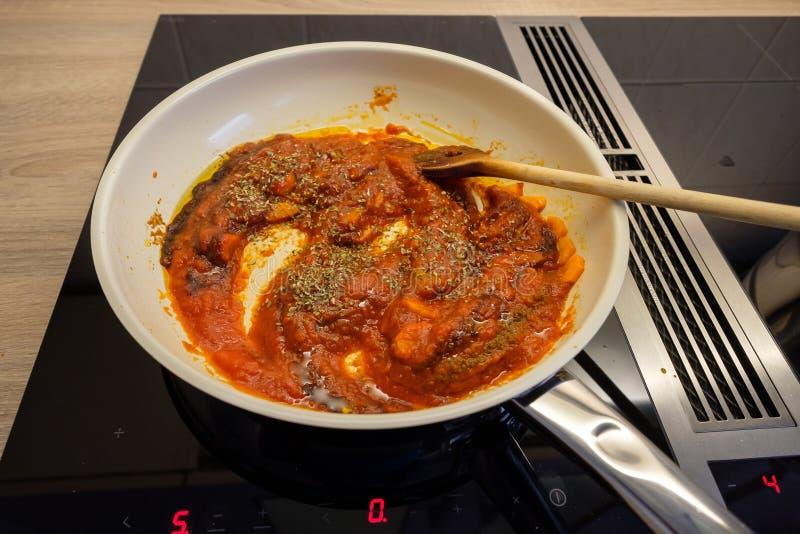 在一个火炉的煎锅与木匙子和西红柿酱 库存照片