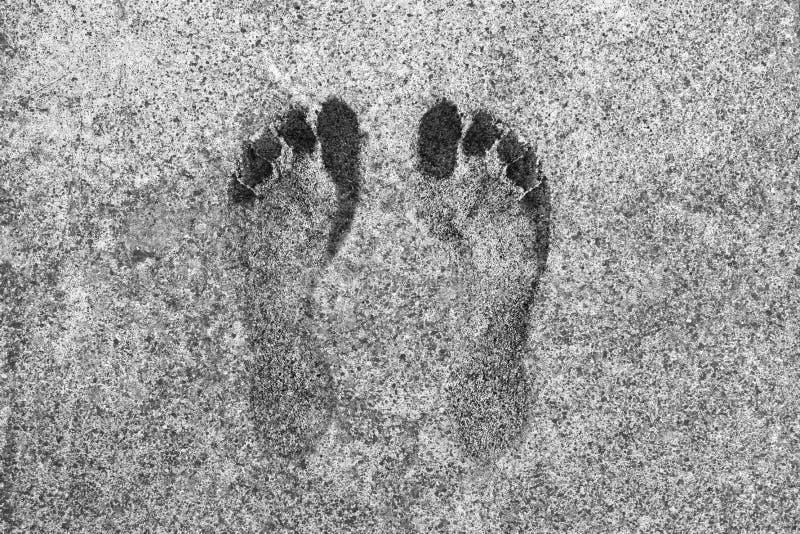 在一个灰色具体盘区的脚印 免版税图库摄影