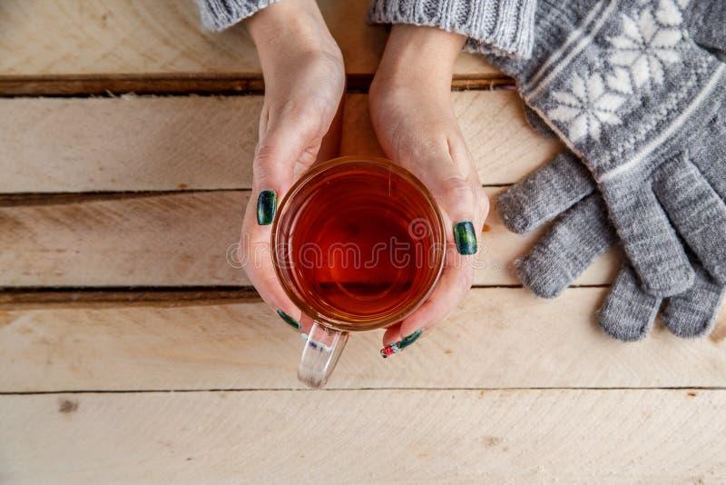 在一个灰色毛线衣和灰色手套的妇女的手拿着透明杯茶 在轻的葡萄酒木背景的顶视图 免版税库存照片