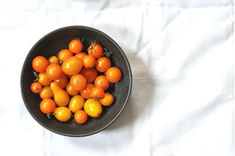 在一个灰色碗的橙色西红柿,中间偏左,白色背景 免版税库存照片