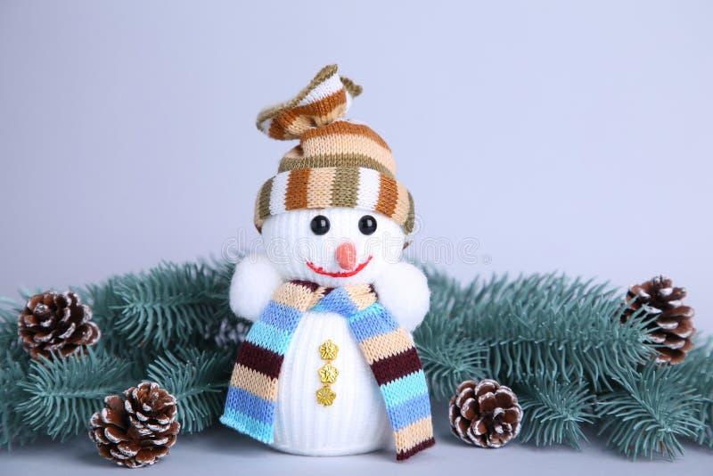 在一个灰色背景wuth冷杉木分支的小雪人玩具 免版税库存图片