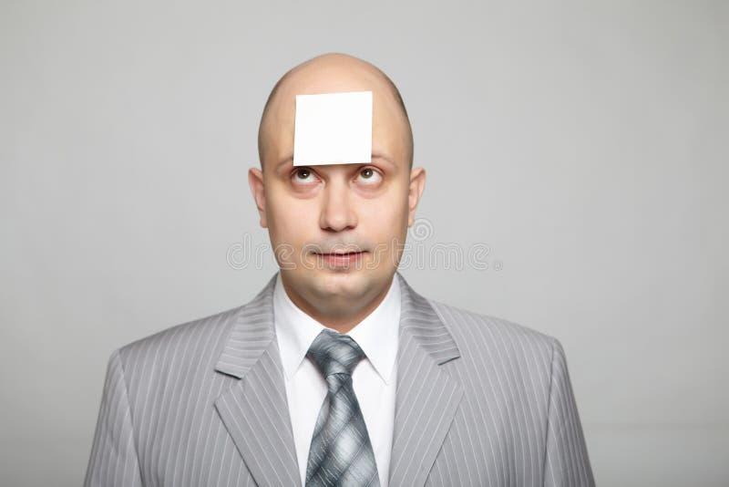 在一个灰色诉讼的秃头生意人 库存图片