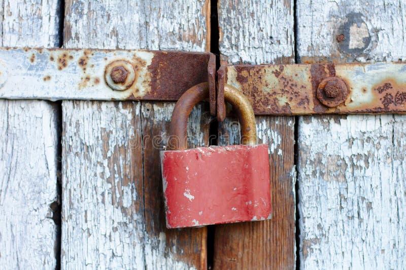 在一个灰色门的老棕色挂锁与破裂的油漆和铁锈葡萄酒门木板条有金属条纹和螺栓的 免版税库存照片