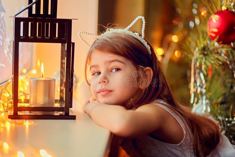 在一个灼烧的蜡烛附近的小女孩 圣诞前夕礼品节假日许多装饰品 免版税库存照片