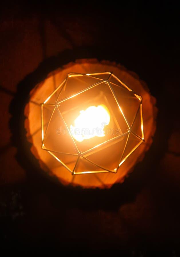 在一个烛台的手工制造蜂蜡蜡烛在木切片 图库摄影