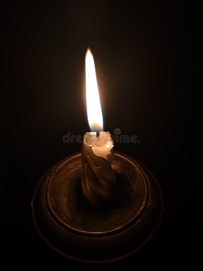 在一个烛台的燃烧的蜡烛在黑背景 库存照片