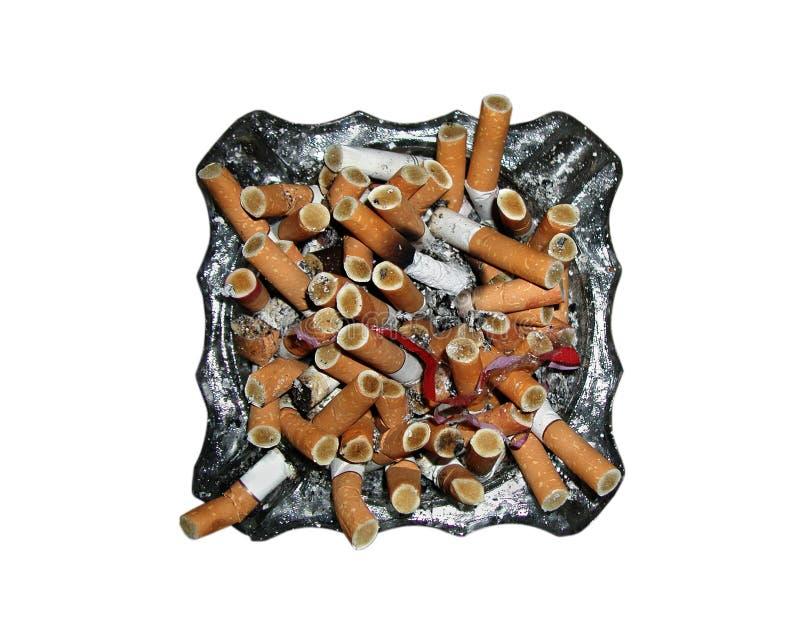 在一个烟灰缸的很多烟头在白色 免版税库存图片