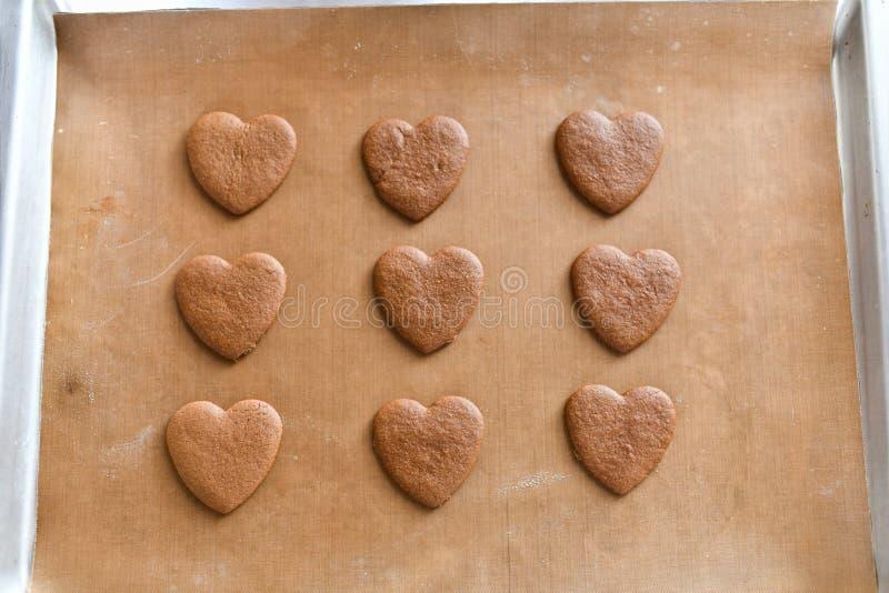 在一个烤板的巧克力饼干,心形的曲奇饼在家烹调了 库存照片